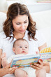 Attentive mother reading a book to her adorable baby