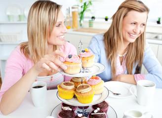Women having fun eating cupcakes in the kitchen