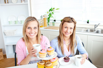 Portrait of two attractive women with coffee and cupcakes
