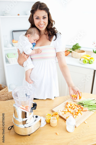 Smiling mother holding her sleeping child while preparing carrot