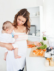 Young mother holding her baby while preparing carrot for lunch