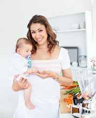 Portrait of a radiant mother holding her baby in kitchen