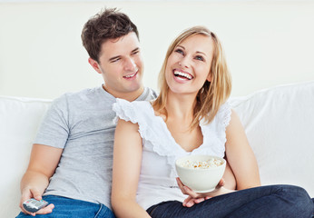 Cheerful couple watching a movie with popcorn  at home