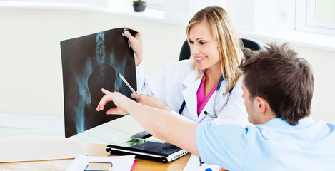 Joyful female doctor showing an x-ray to a patient