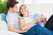 Joyful woman receiving a surprise from her boyfriend at home