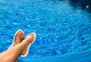 Feet in beach slippers on the brink of pool