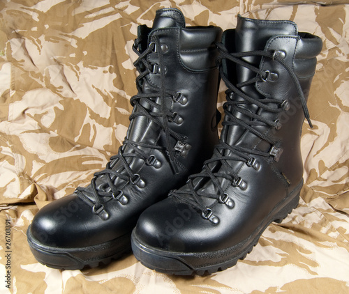 black leather boots on desert camouflage background