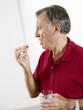 senior man eating pills