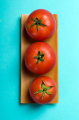 ripe tomatoes on blue background