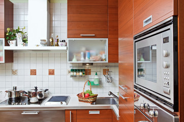 Part of Kitchen interior with wooden furniture and build in micr