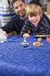 Boy with father spinning dreidel