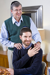 Senior Jewish man with adult son wearing yarmulkes