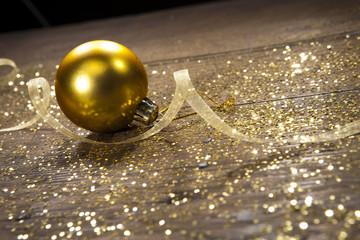boule de noel dorée avec ruban et paillettes sur table en bois