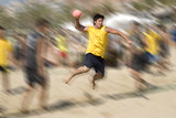 Beach handball player jumping with ball