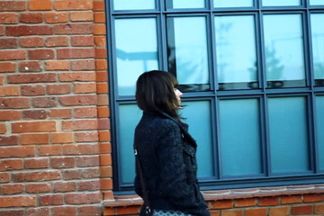 Woman walking by the brick wall, steadicam shot, shot at 60fps
