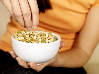 Young Woman Eating Mixed Seeds. Model Released