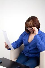 Девушка внимательно смотрит на документ поверх очков
