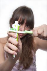 Перекрещенная зубная паста и щетка в руках девушки