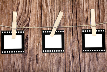 old film blanks hanging on a rope held by clothespins over wood