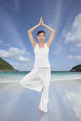 Asian woman doing yoga on the beach
