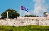 The walls of a fortress in Havana with a waving Cuban flag