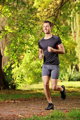 Male athlete jogging on a trail in the park