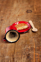 overturned espresso coffee in red enamel mug with saucer, woode