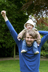 Happy father carrying baby on his shoulders