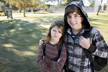 Teenage boy and young sister with school backpacks