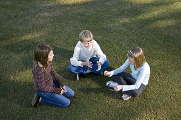 Children sitting in a circle on grass talking