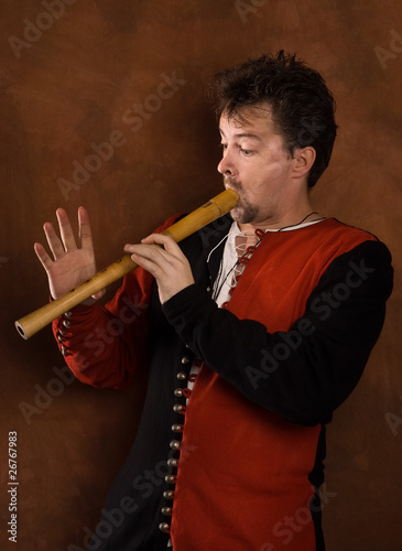 Man in a medieval suit plays a flute