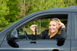 Cheerful woman with keys from car