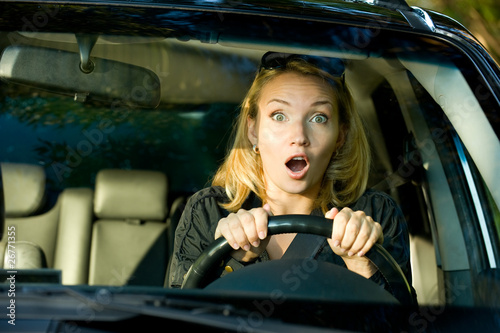 Fright face of woman driving car - inside