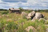 Pile of big stones in green grass before wooden hut