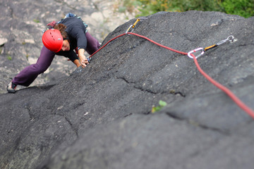 Young woman with helmet climbing basalt rock