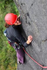 Smiling woman with helmet climbing basalt rock