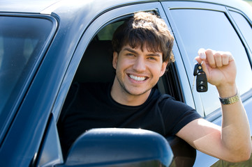happy man showing keys from car