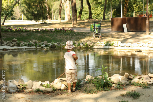 The little boy fishes in a pond (plays)