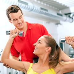 Frau mit Hanteln und Trainer im Fitnessstudio