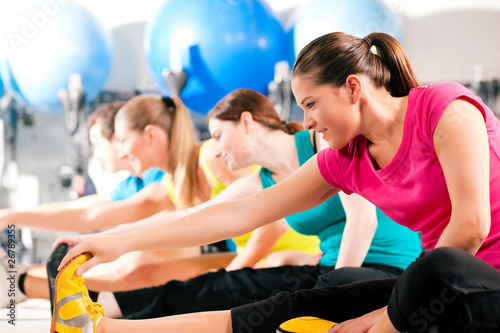 People in gym warming up stretching