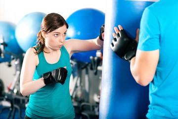 Kick-Boxerin mit Trainer am Sandsack
