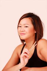 Smiling asian female holding chopsticks