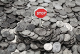 "Heap of coins and sign ""Stop"""
