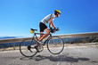 Cyclist riding a bike uphill along a road; clear summer day