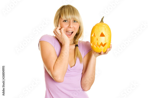 Girl terrified screams with a pumpkin for Halloween