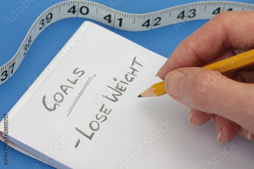 Hand with Pencil making goals list to lose weight