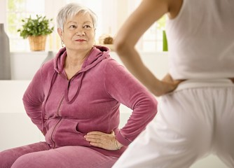 Elderly woman looking at personal trainer