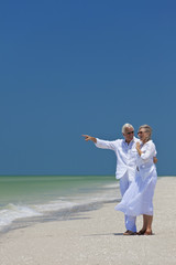 Happy Senior Couple Pointing To Sea on Tropical Beach