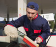 Gas Station Worker Cleaning Windshield at Service Station