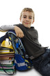 Schoolboy sitting on floor, lean on school bag and books